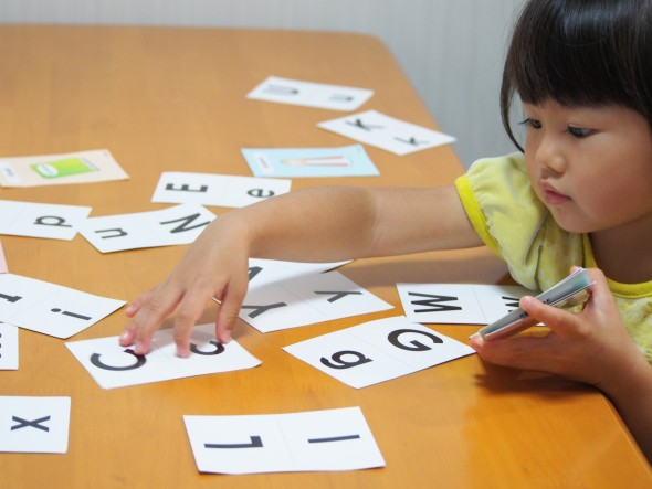 アルファベットカードで遊ぶ女の子