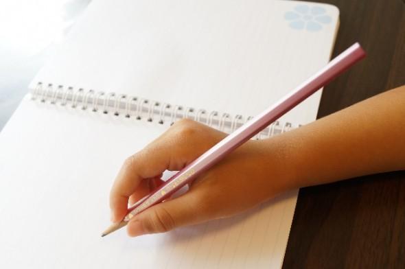 ノートを書く子どもの手