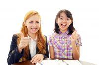 ガッツポーズをして喜ぶ英会話講師と小学生
